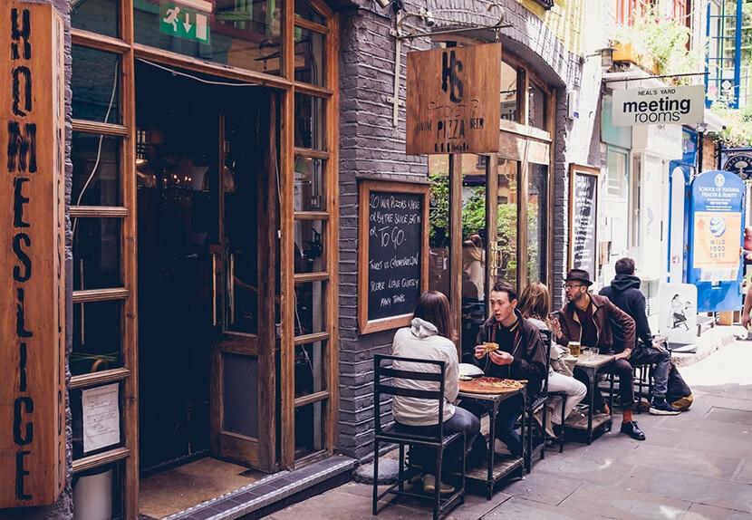 אנשים יושבים ואוכלים מחוץ לפיצרייה. הומסלייס פיצה (צילום: Charlie McKay)