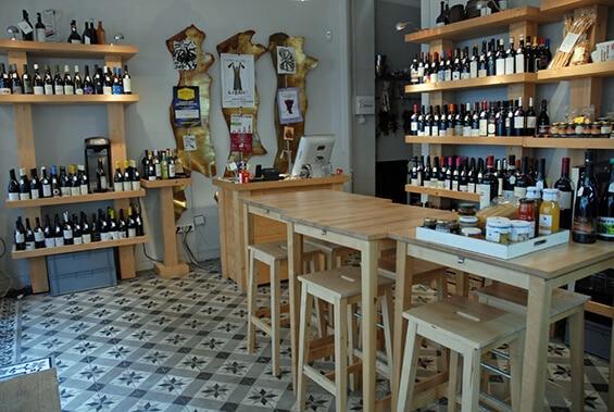 מדפים עם בקבוקי יין ושולחן בתוך החנות. אגרולוז'י (צילום: יפה עירון-קוץ)